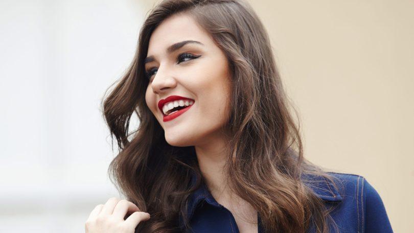 Mulher com cabelos pretos lisos e pontas ondulados