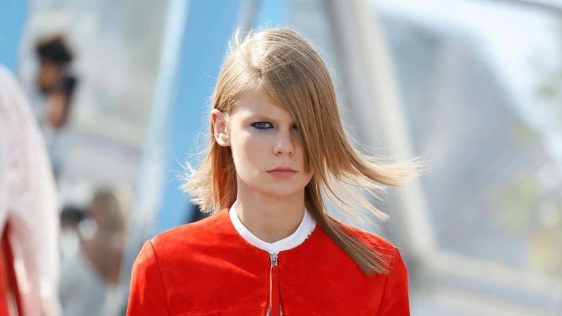 Mulher com cabelo loiro e liso esvoaçante usa casaco vermelho e ilustra matéria sobre cabelo e poluição