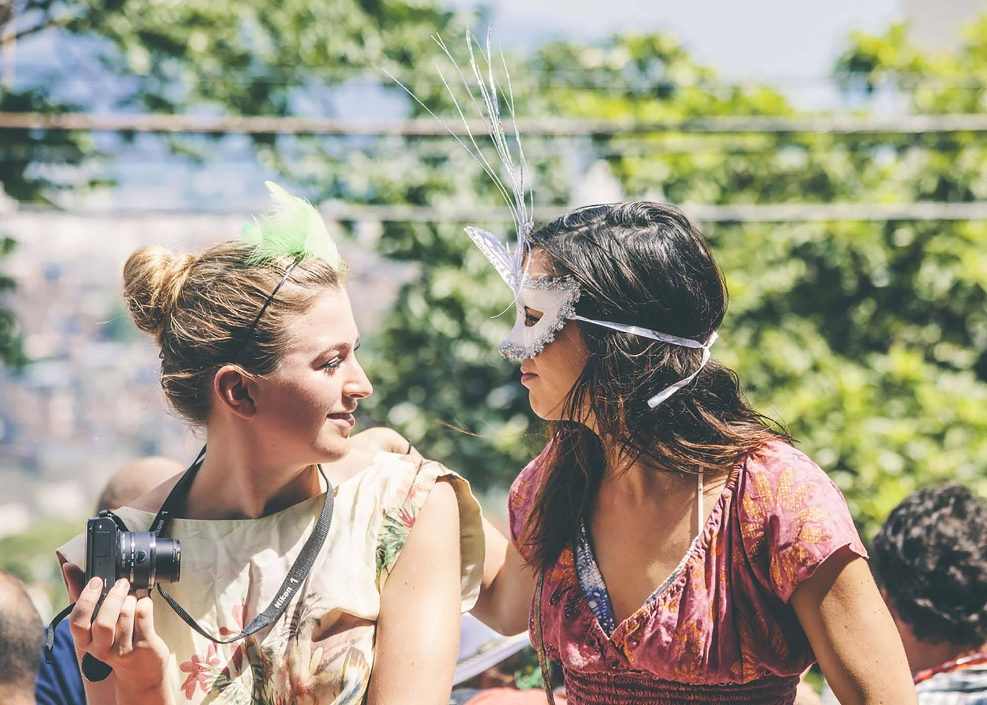 Duas meninas fantasiadas conversam, uma com um coque no cabelo e outra com cabelo solto, elas ilustram matéria sobre Cabelo para o Carnaval da sua vida