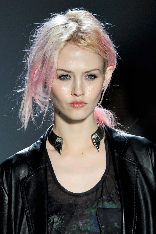 Mulher usa jaqueta preta, tem o cabelo com mais de um tom, platinado e rosa claro.