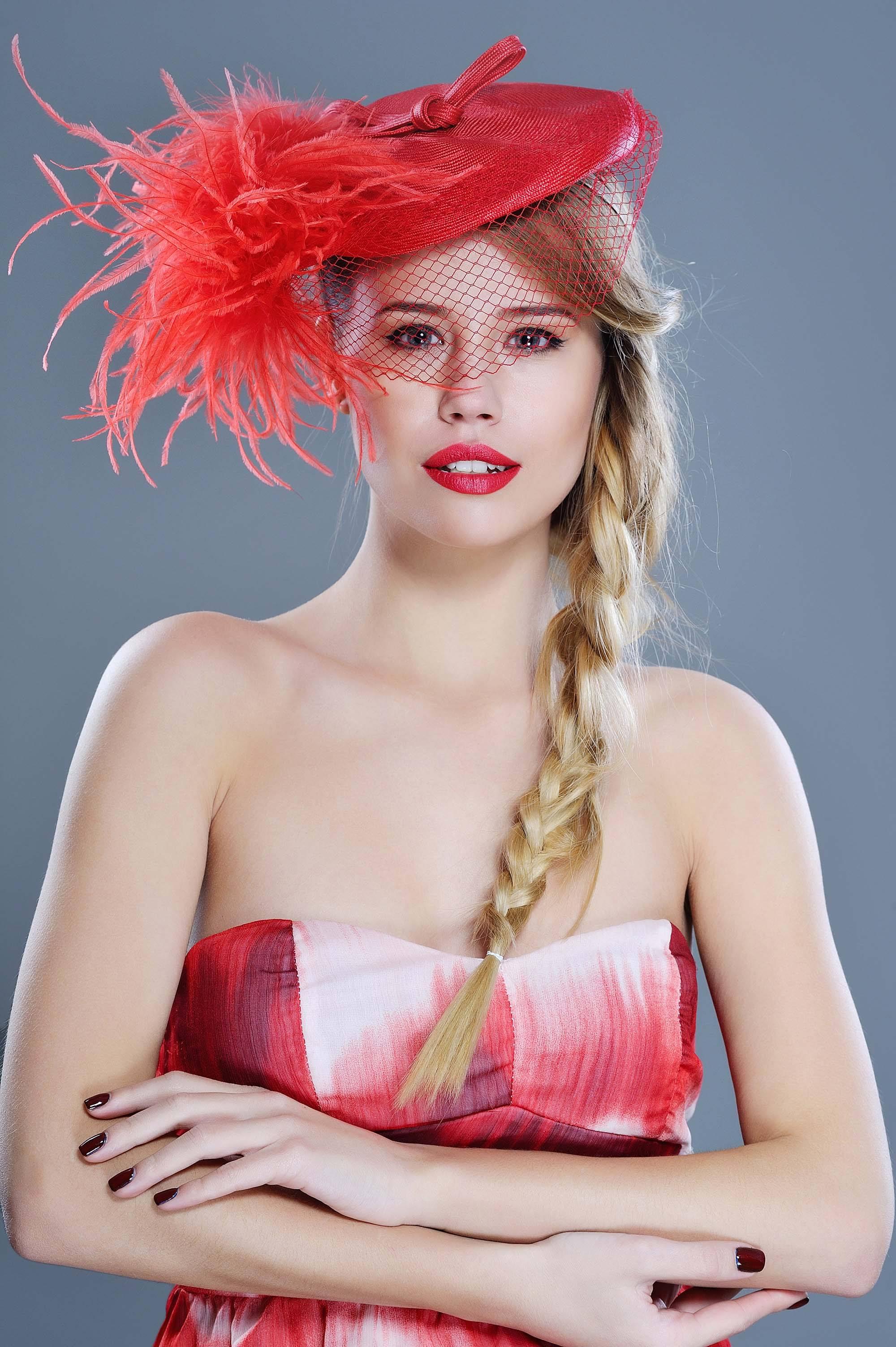Mulher usa vestido branco e vermelho e casquete vermelha com pensas no cabelo