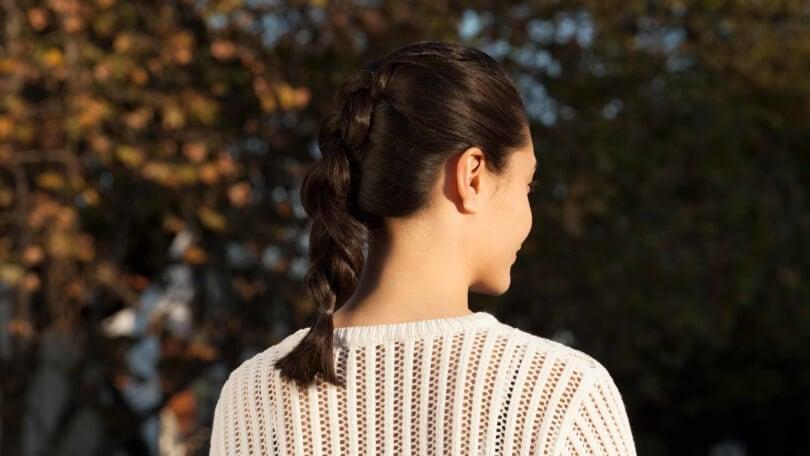 Mulher de cabelo preto posa ao ar livre e ilustra matéria sobre penteados para o happy hour.
