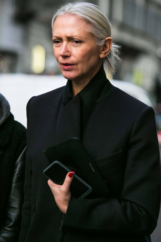 Mulher com cabelo cinza usa roupa preta e pun no cabelo