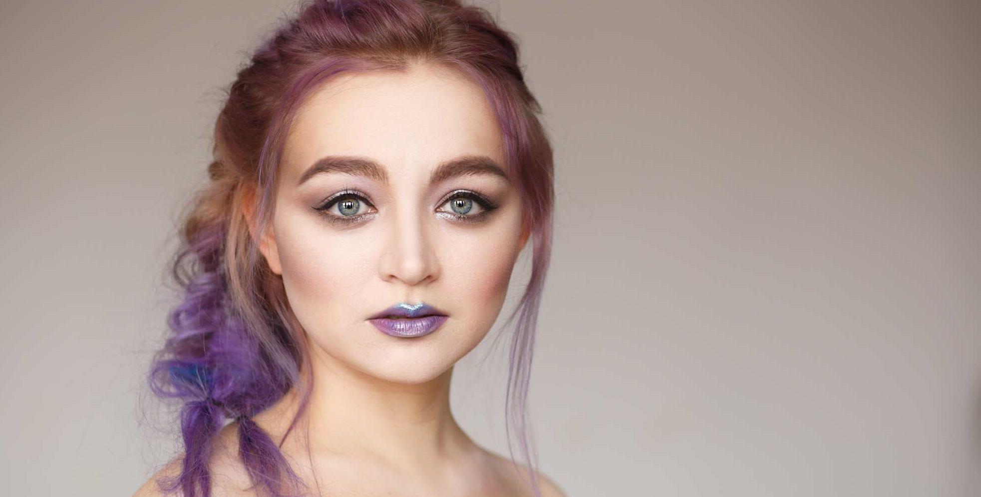 Mulher usa cabelo roxo e lilás, ton sur ton, com rabo de cavalo