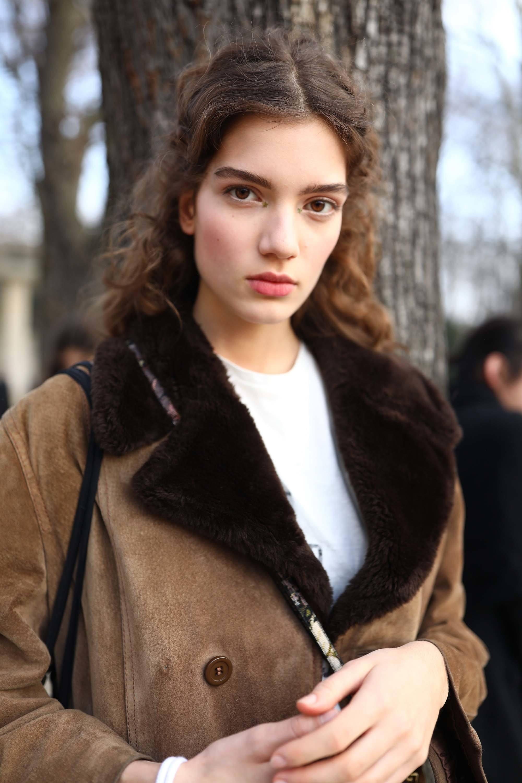 Mulher de cabelo castanho e cacheado usa blusa branca e jaqueta preta e marrom.