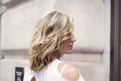 Mulher loira posa ao ar livre, de perfil, com cabelo jogado no rosto e usando uma blusa branca com decote nos ombros.