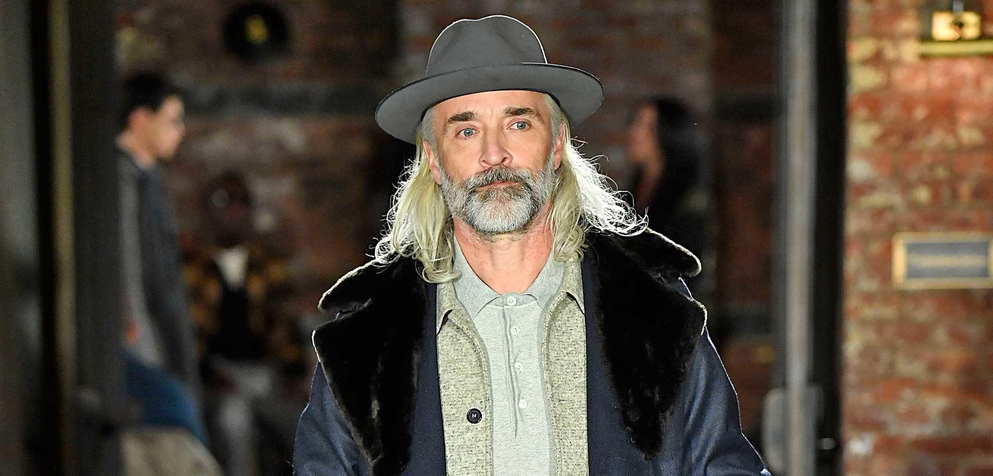 Homem de cabelo comprido e branco desfila na NYFW, com chapéu, camisa cáqui e sobretudo azul