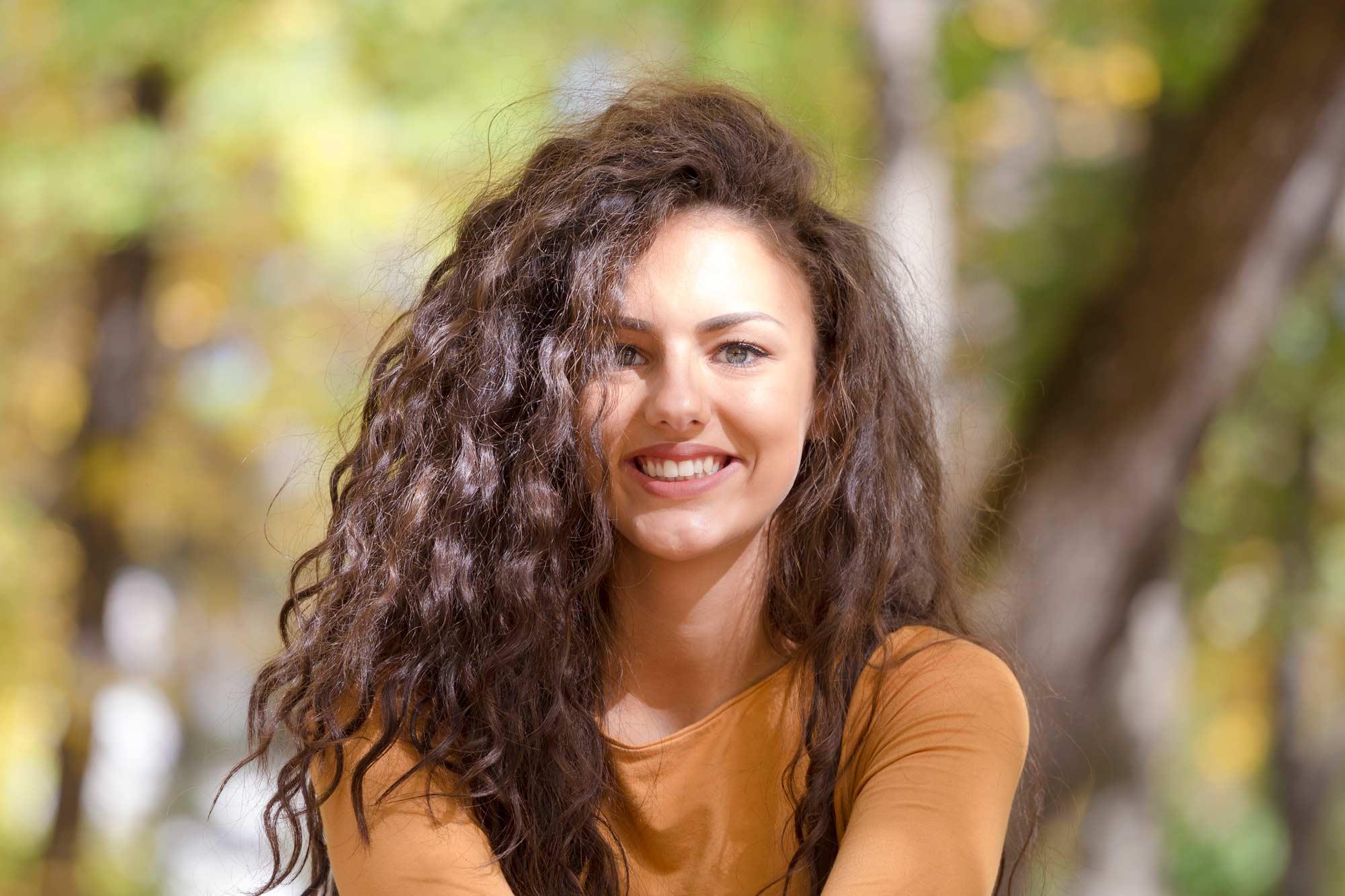 modelo com cabelo cacheado sorrindo: secar cabelo cacheado com ventilador