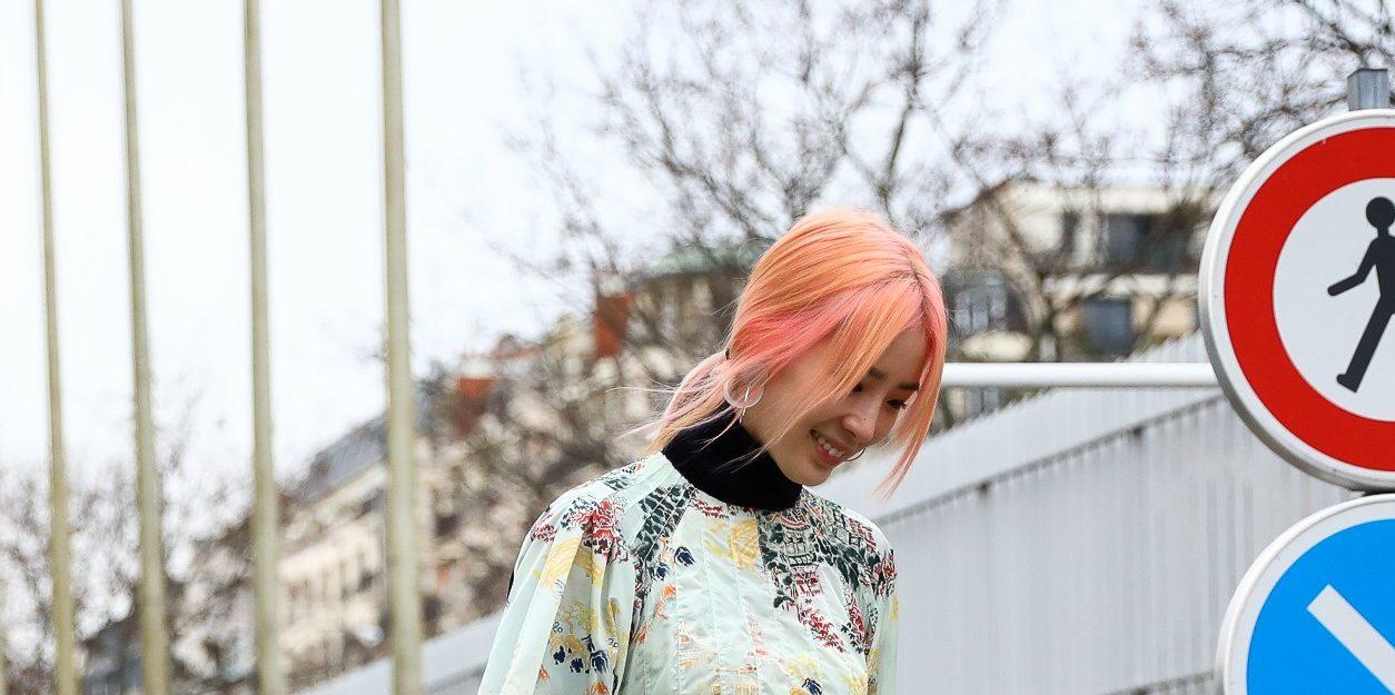 Mulher usa cabelo rosa e anda pela rua com vestido verde água