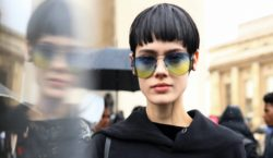 Mulher usa cabelo curto e moletom preto, além de óculos escuros azuis e amarelos