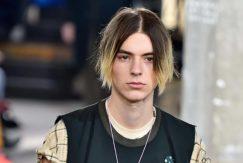Modelo com cabelo de comprimento médio para matéria de cabelo masculino ao meio