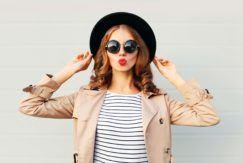 Modelo ruiva com chapeu e óculos escuros para matéria sobre frequência de corte de cabelo
