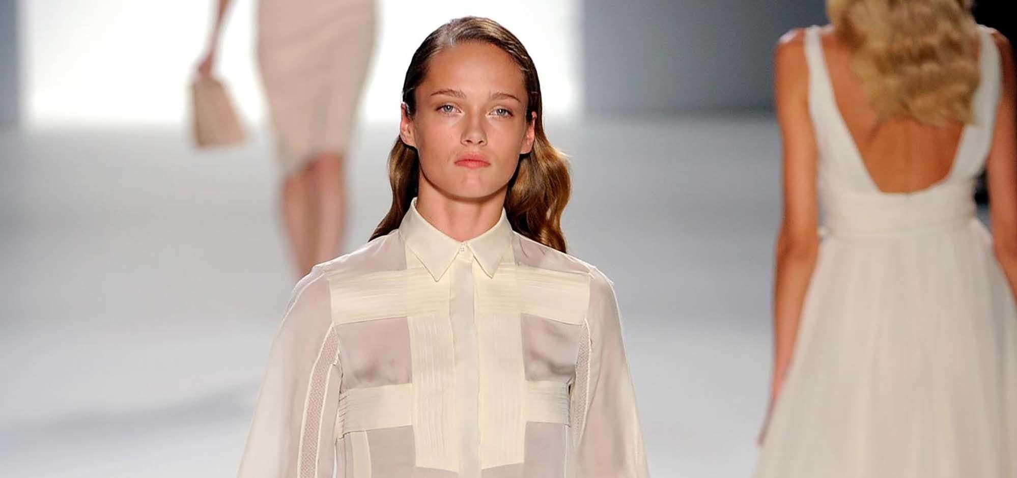 Modelo loira desfila usando roupa branca na passarela