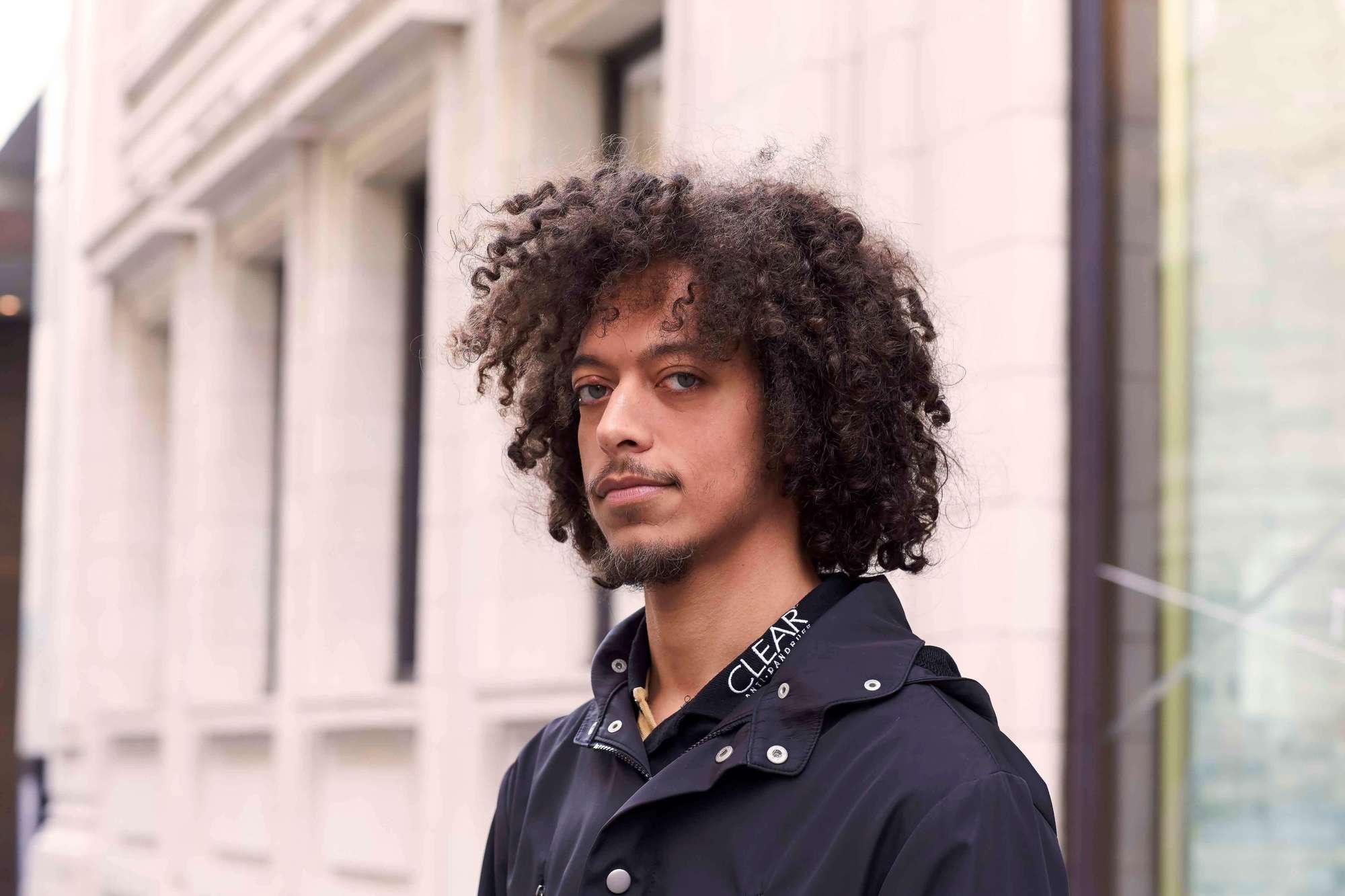 modelo com cabelo crespo ilustrando a matéria sobre como fazer o cabelo crespo masculino crescer