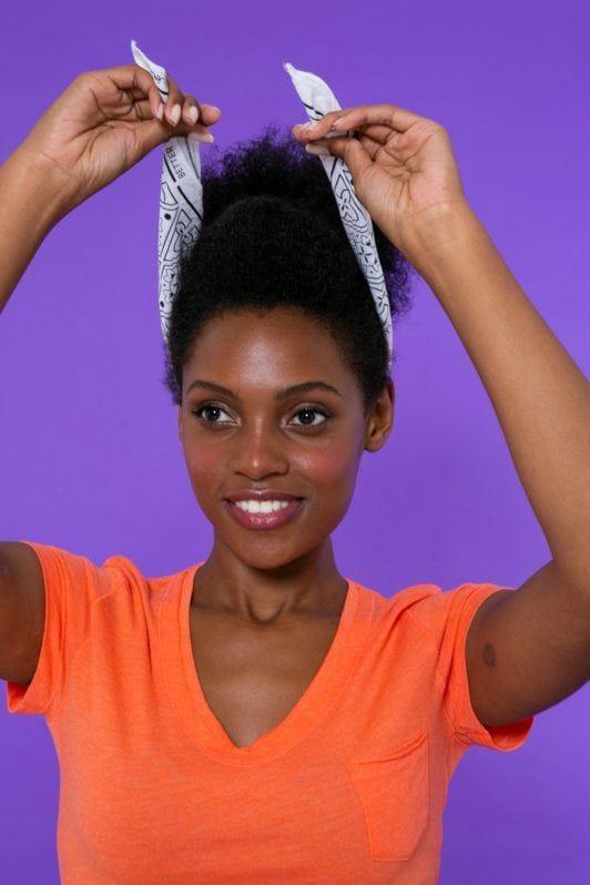 modelo de cabelo crespo preso posicionando um lenço na cabeça