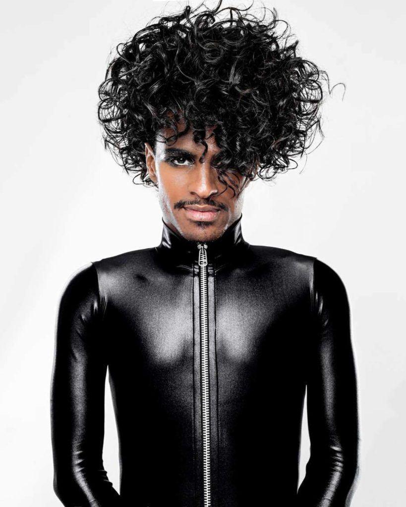 Rico Dalasam com cabelo cacheado preto