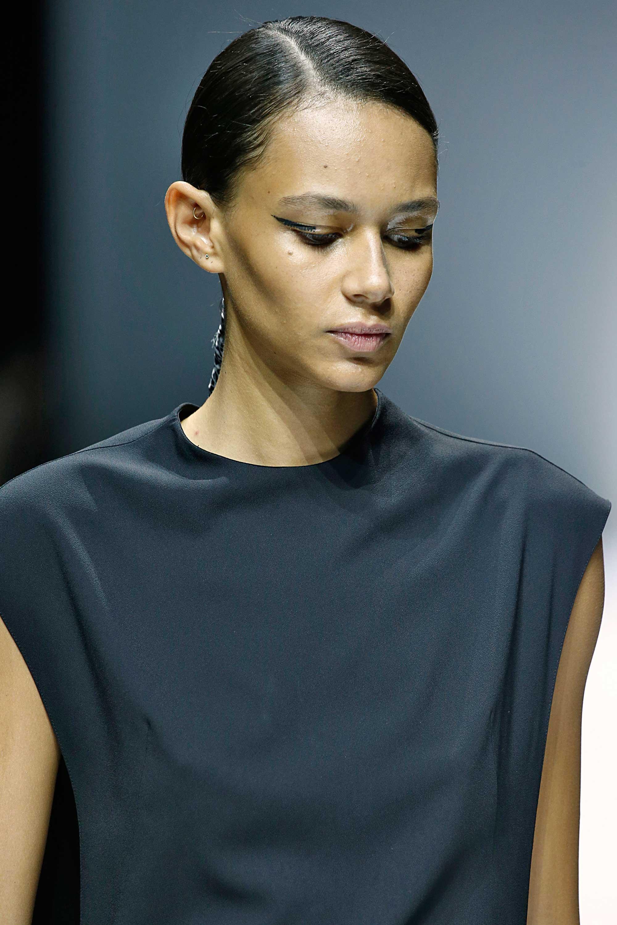 modelo usando um dos penteados para cabelos cacheados e crespos com a raiz polida
