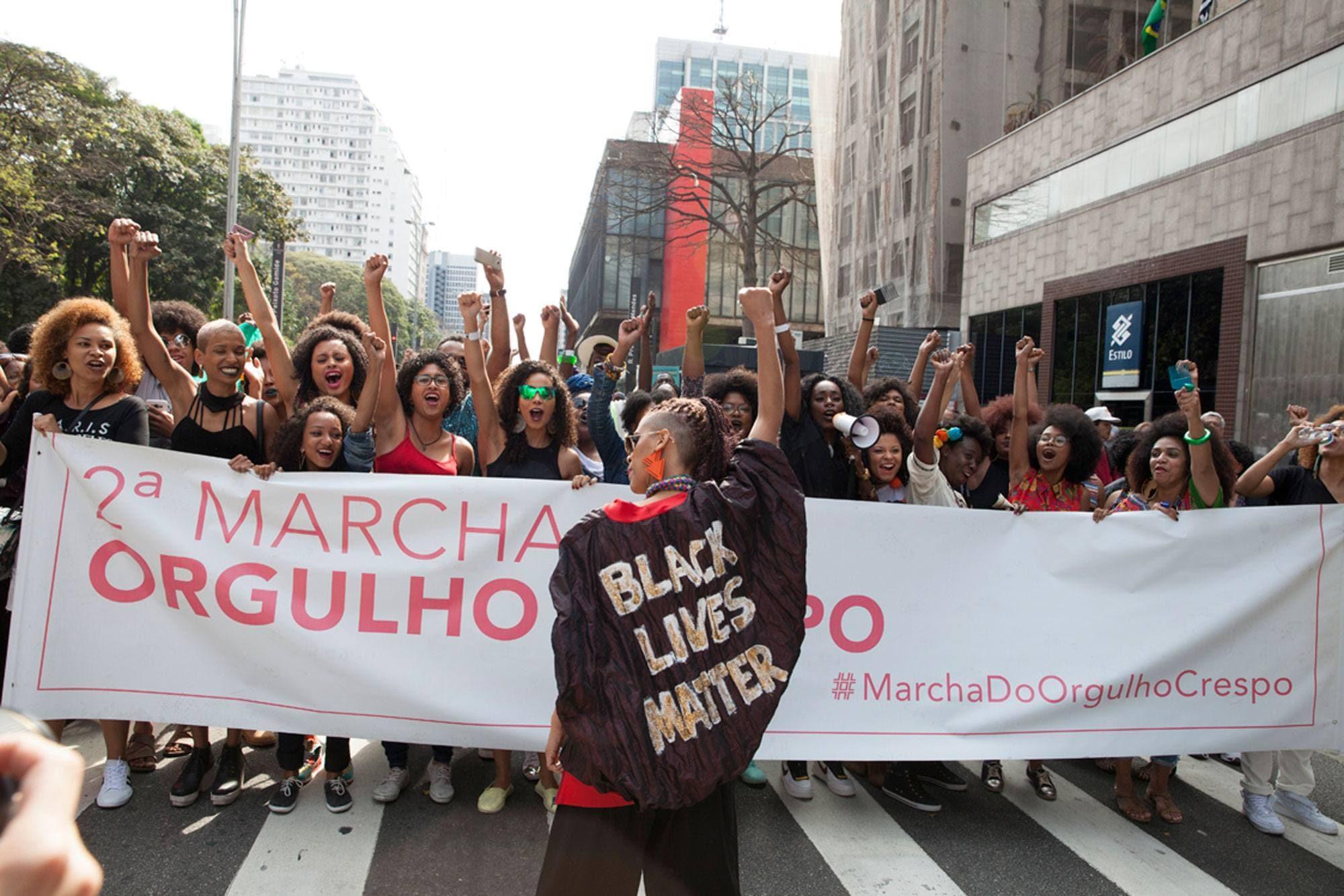 Mulheres e homens de cabelo crespo reunidos na marcha do orgulho crespo