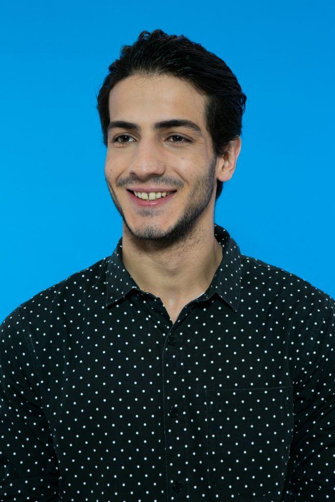 modelo masculino em fundo azul de cabelo preto curto