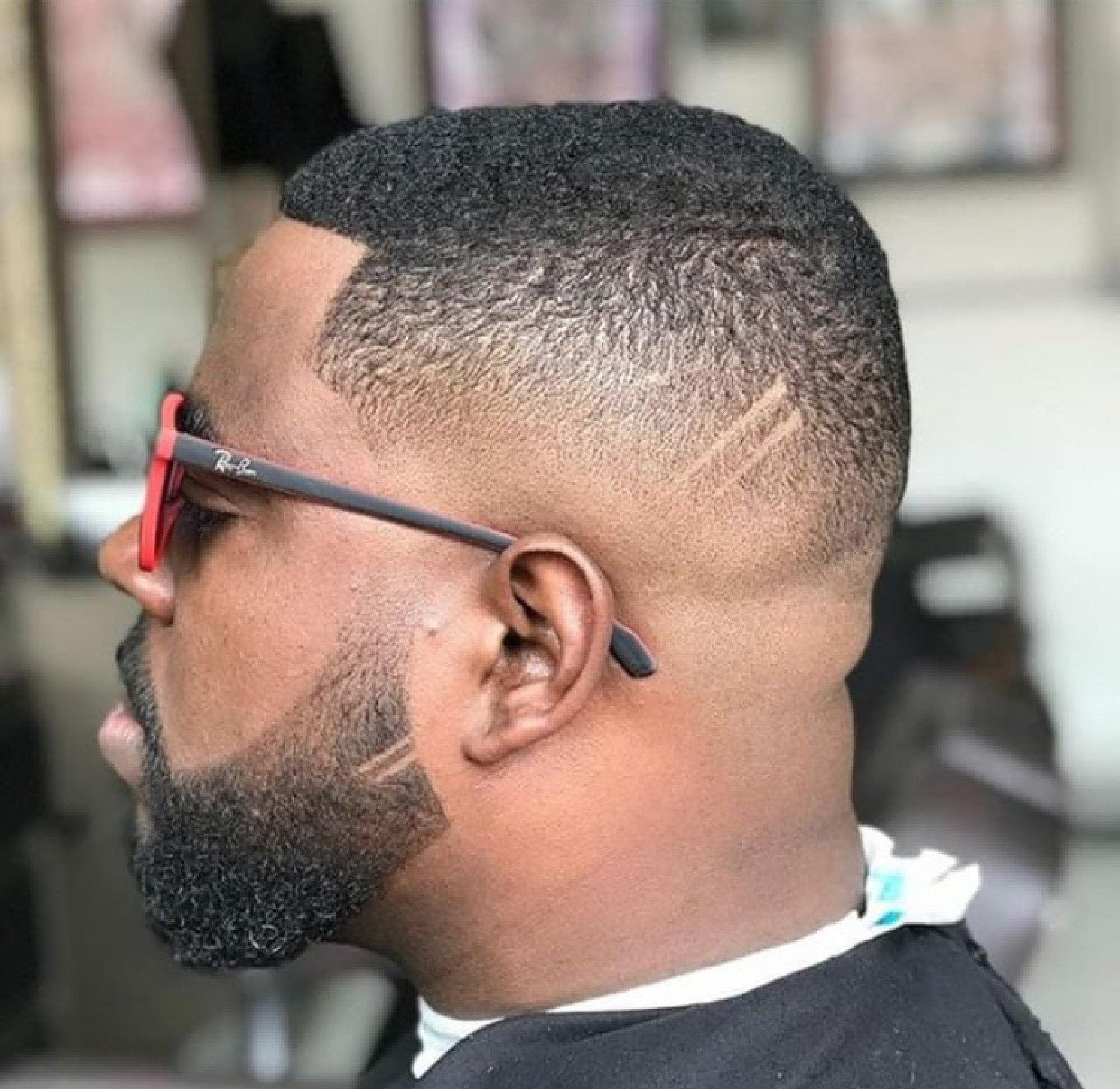 Homem com cabelo curto degradê crespo e óculos escuros