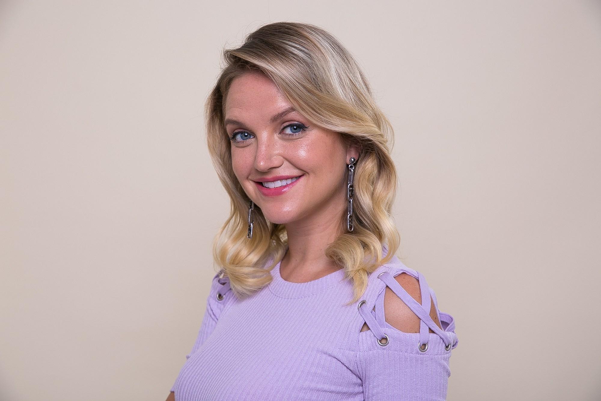 Modelo com cabelo médio loiro ondulado e blusa lilás com detalhes vazados nos ombros
