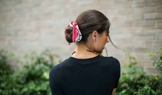 modelo com cabelo preso em um coque com lenço
