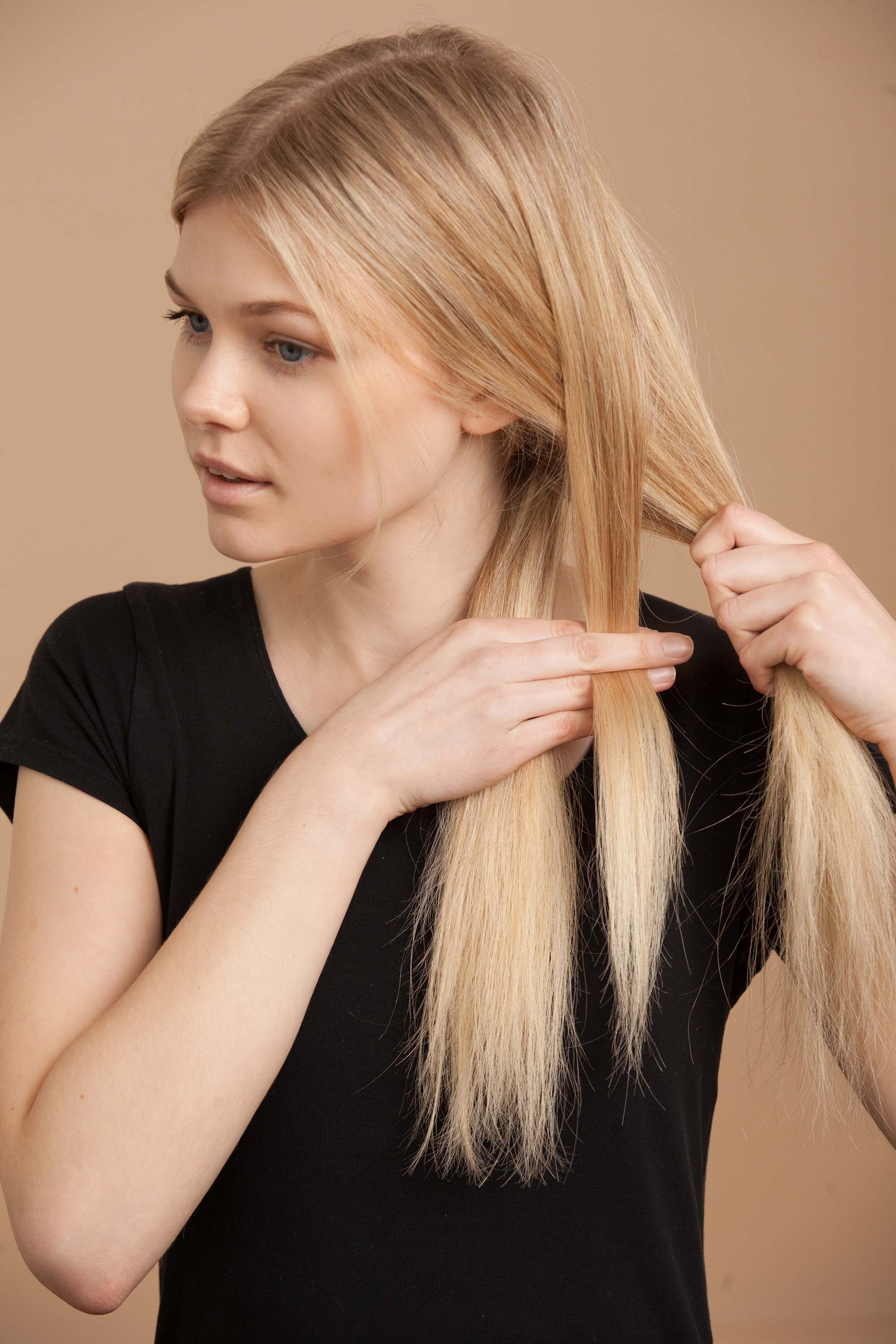 blonde woman creates fishtail braid and creates second section