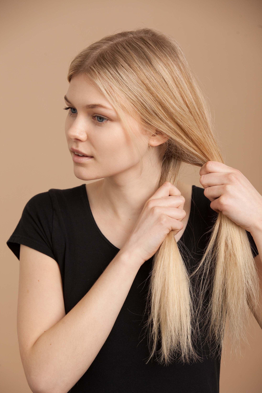 blonde woman creates fishtail braid and separates hair
