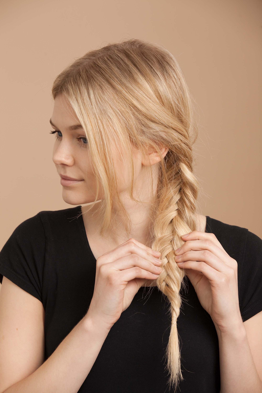 blonde woman creates fishtail braid and pulls braid