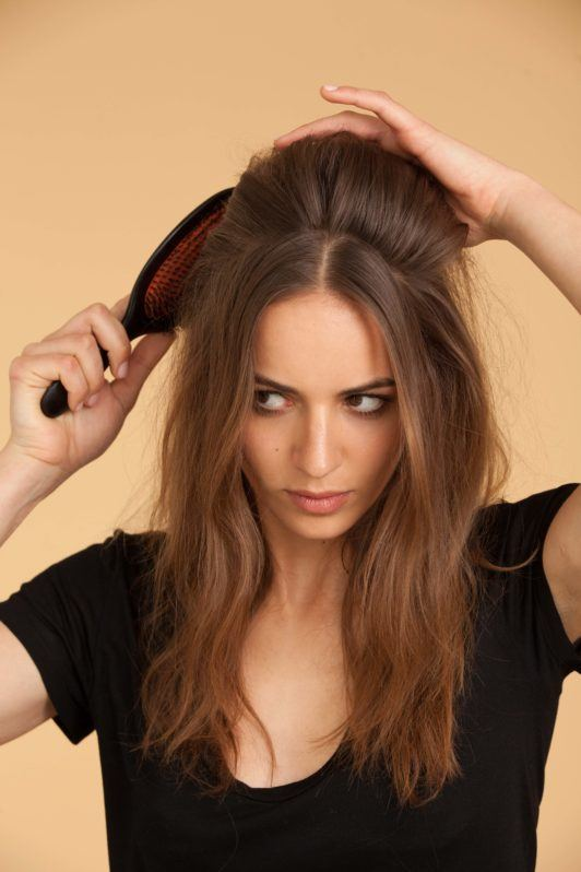 woman with light brown hair creates beehive hair and smooths top