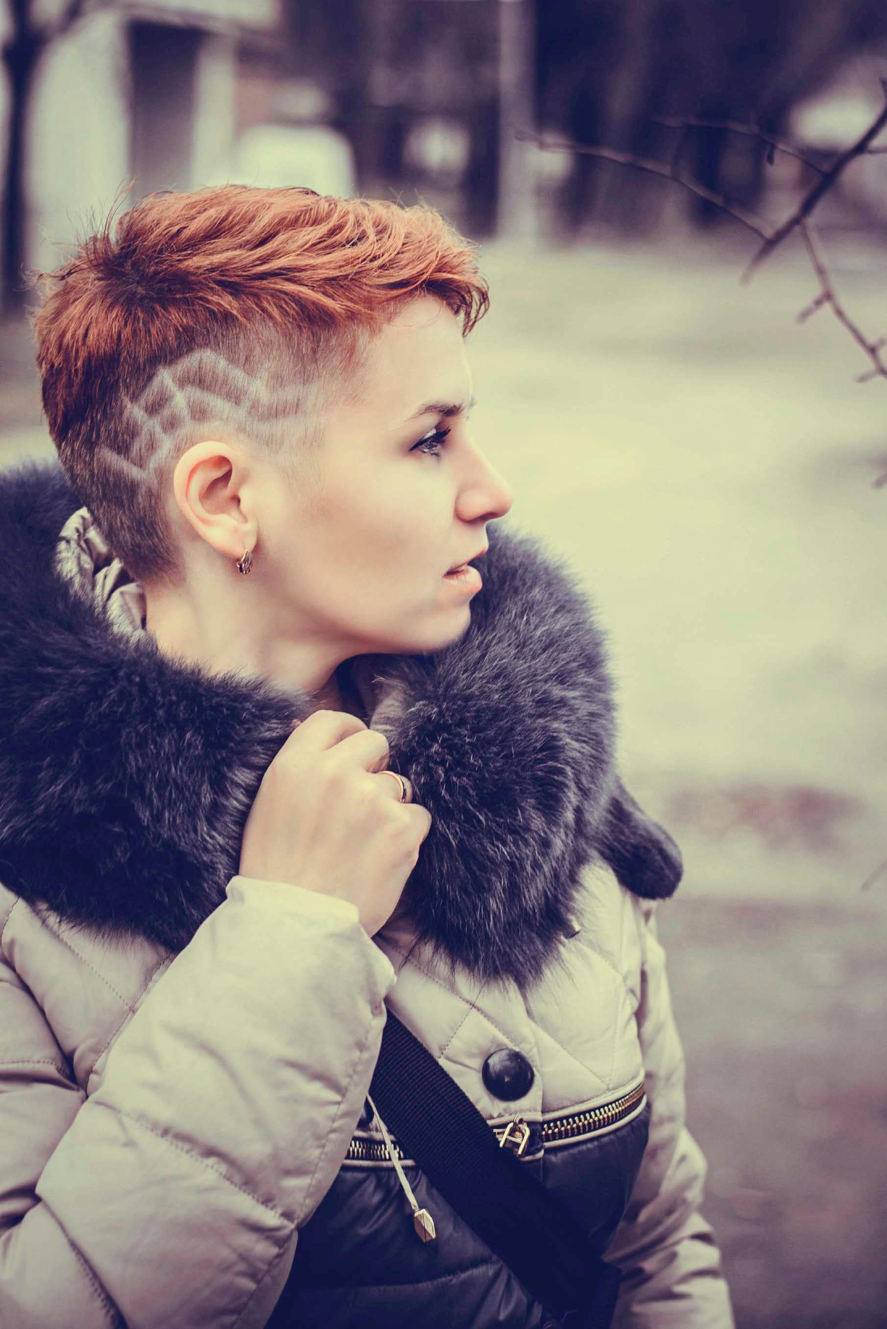 young woman wearing side shaved hair with designs.
