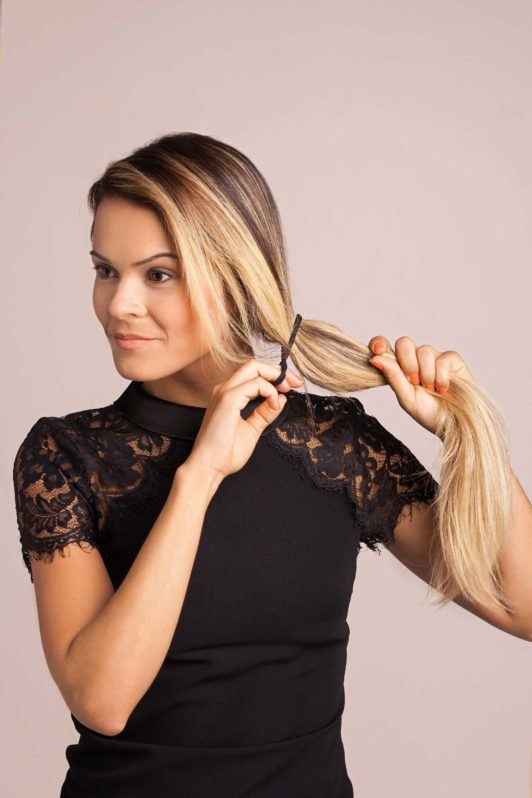 blonde woman creates side fishtail braid hairstyles with a side ponytail