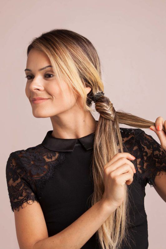 blonde woman creates fishtail side braid hairstyle and begins braiding