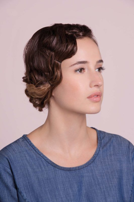 a flapper hairstyle of a woman who is wearing a blue t-shirt from aside