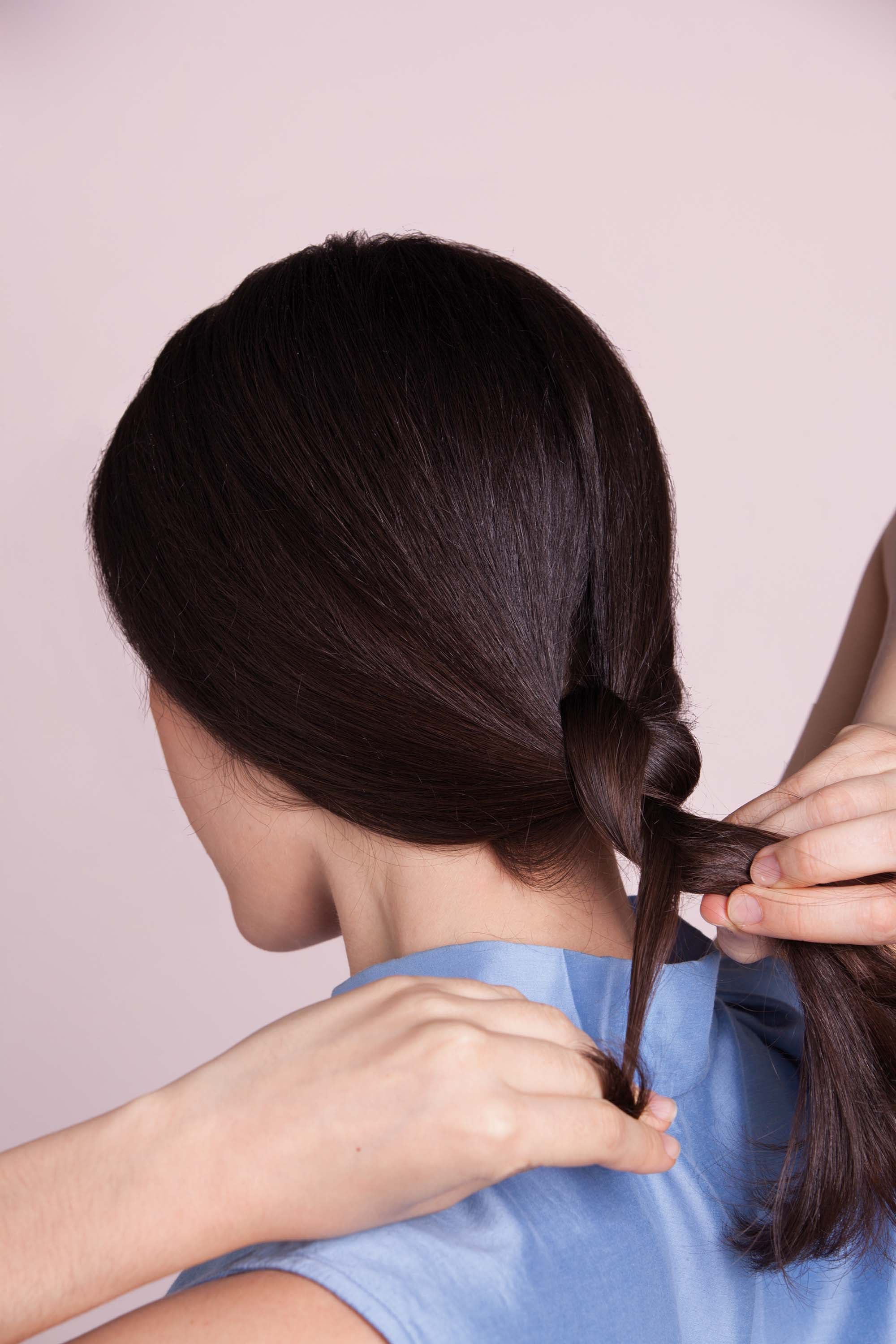 a rear view of a woman twisting her ponytail to wrap over her hair