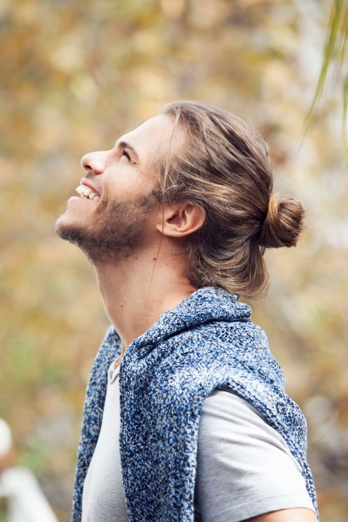 a side view of a smiling man with man-bun