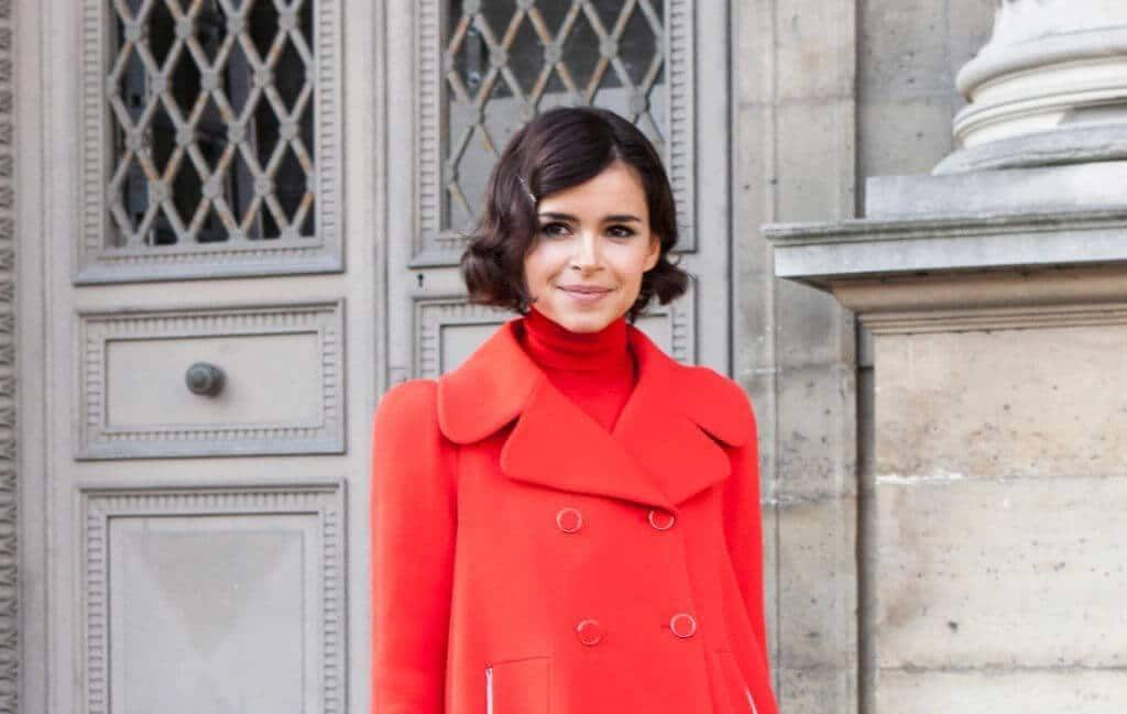 a woman wearing bright red coat smiling in a city with short hairccut