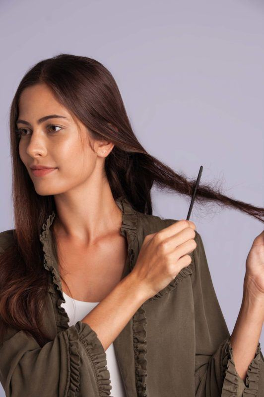 fake dreads - step 2 - woman with long black hair back combing a section