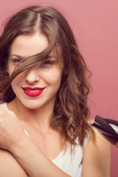 a brown hair woman hair drying her wavy hair while smiling