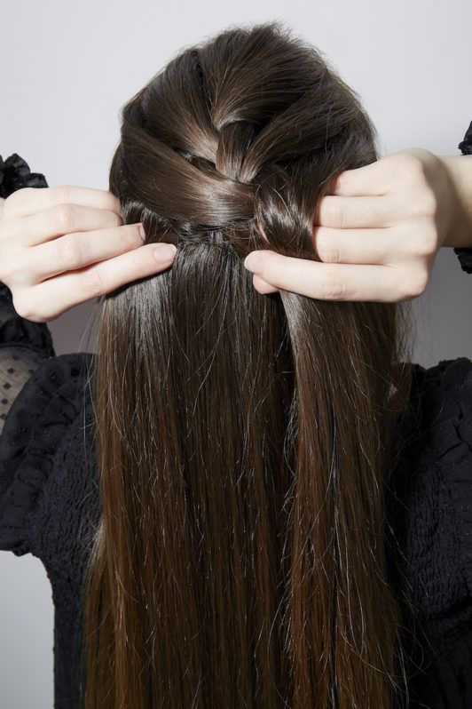 a rear view of a woman making a braid on her long dark hair