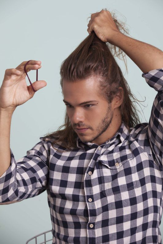 blonde man shows how to make a man bun and grabs hair tie