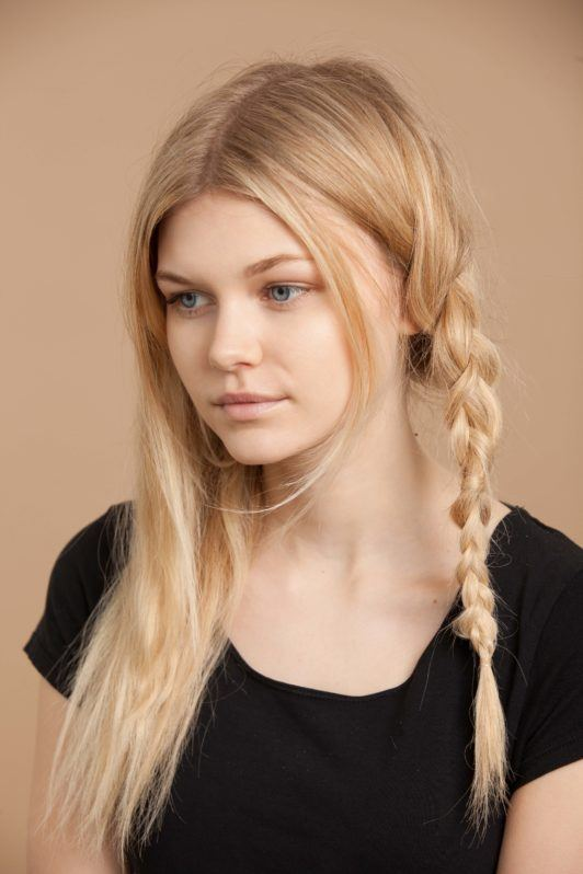 the next step in creating milkmaid braids is securing the braid with a hair tie