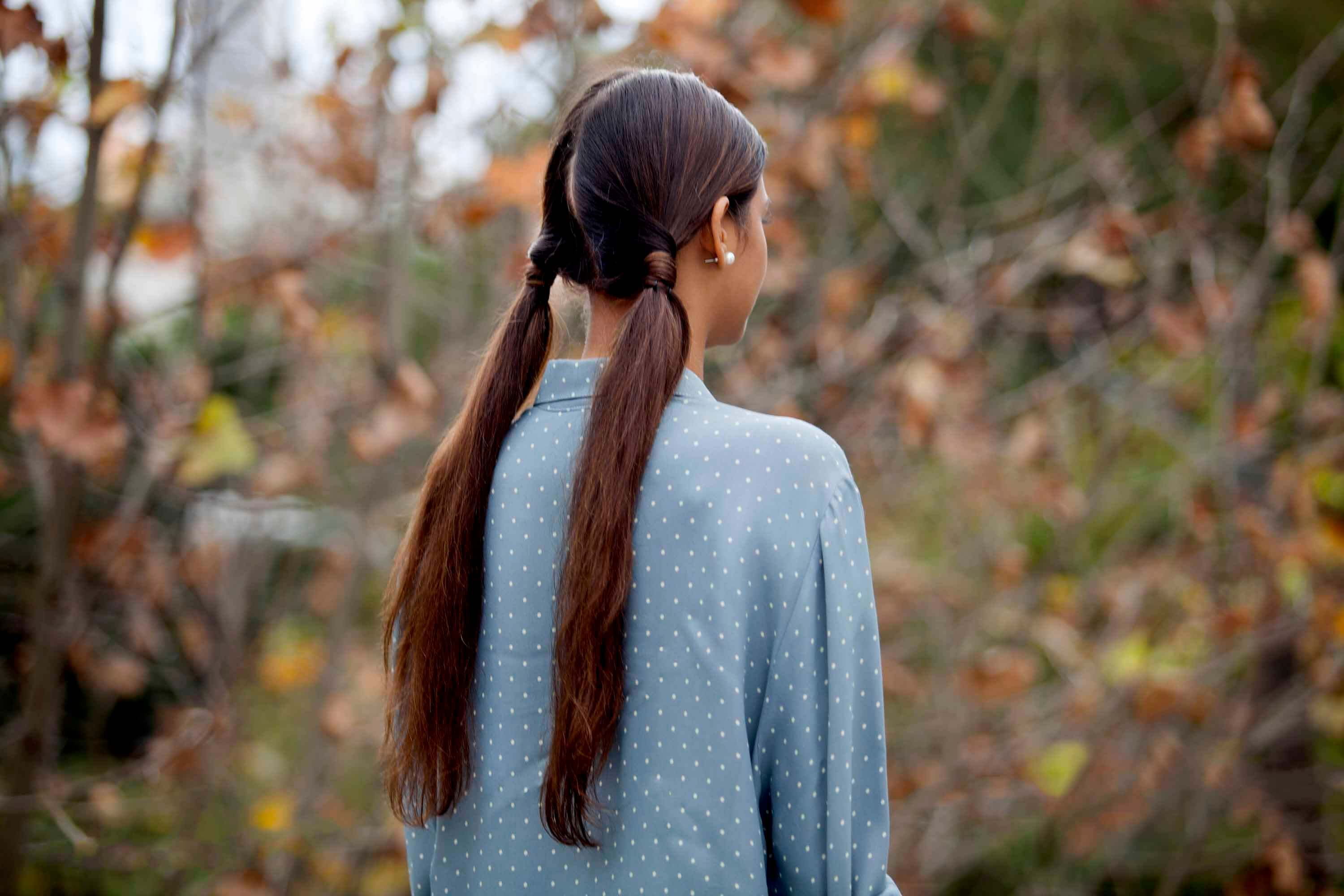 brunette woman wearing low pigtail ponytails outside