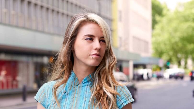 a blonde woman with long wavy hair wearing blue shirt walking on a street in the city