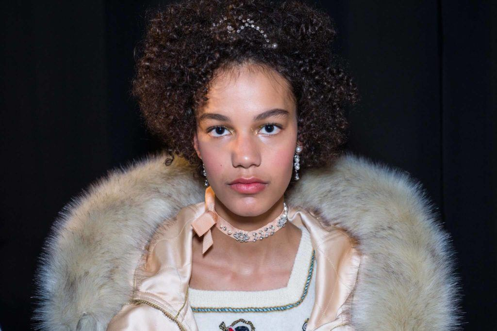 a curly afro woman looking straight wearing fur coat and a tiara accessories