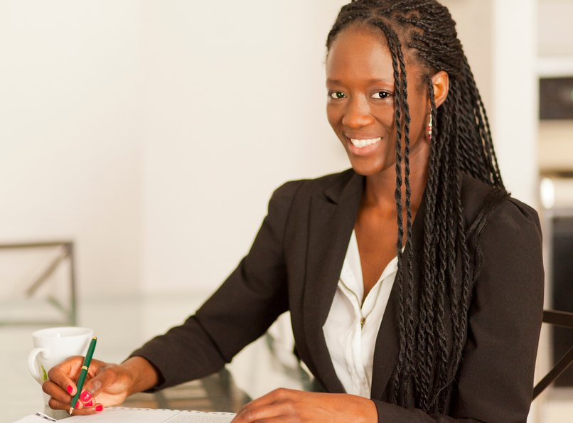 a working wiman with dreadlock long black hair at her office