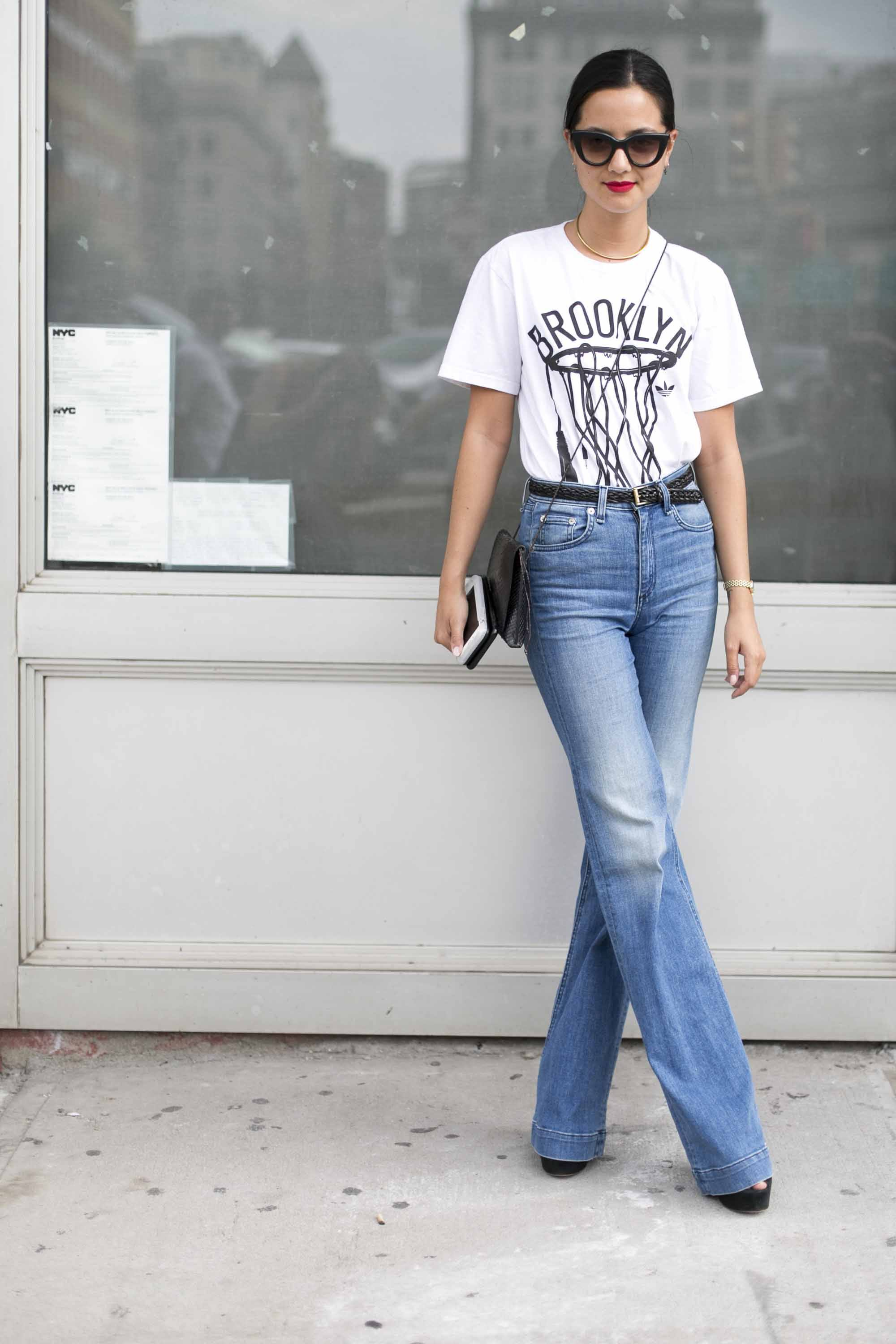 a casual look of a woman standing in front of a store wearing jeans and white t-shirt