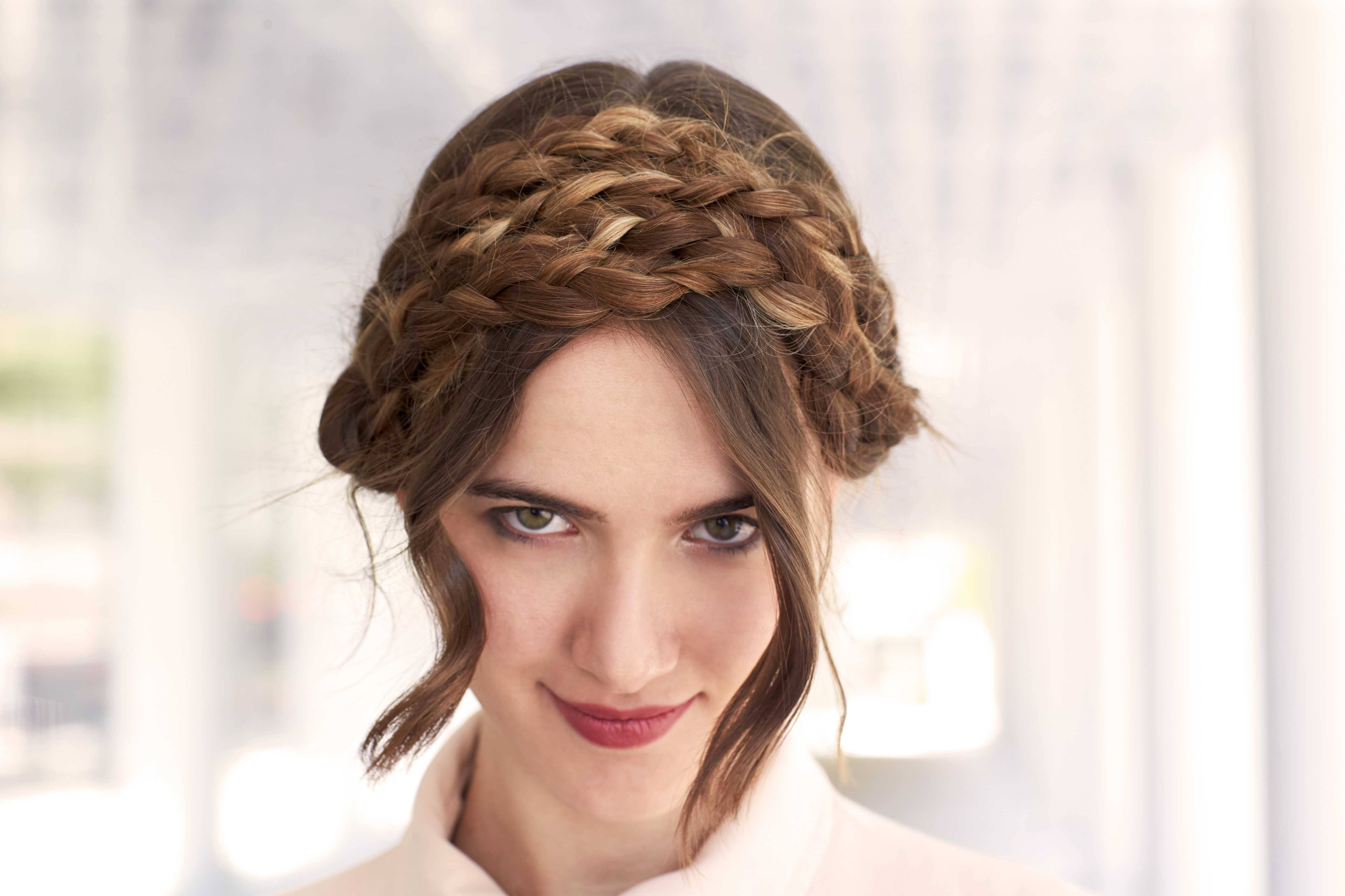 woman with milkmaid braids hairstyle and curly bangs