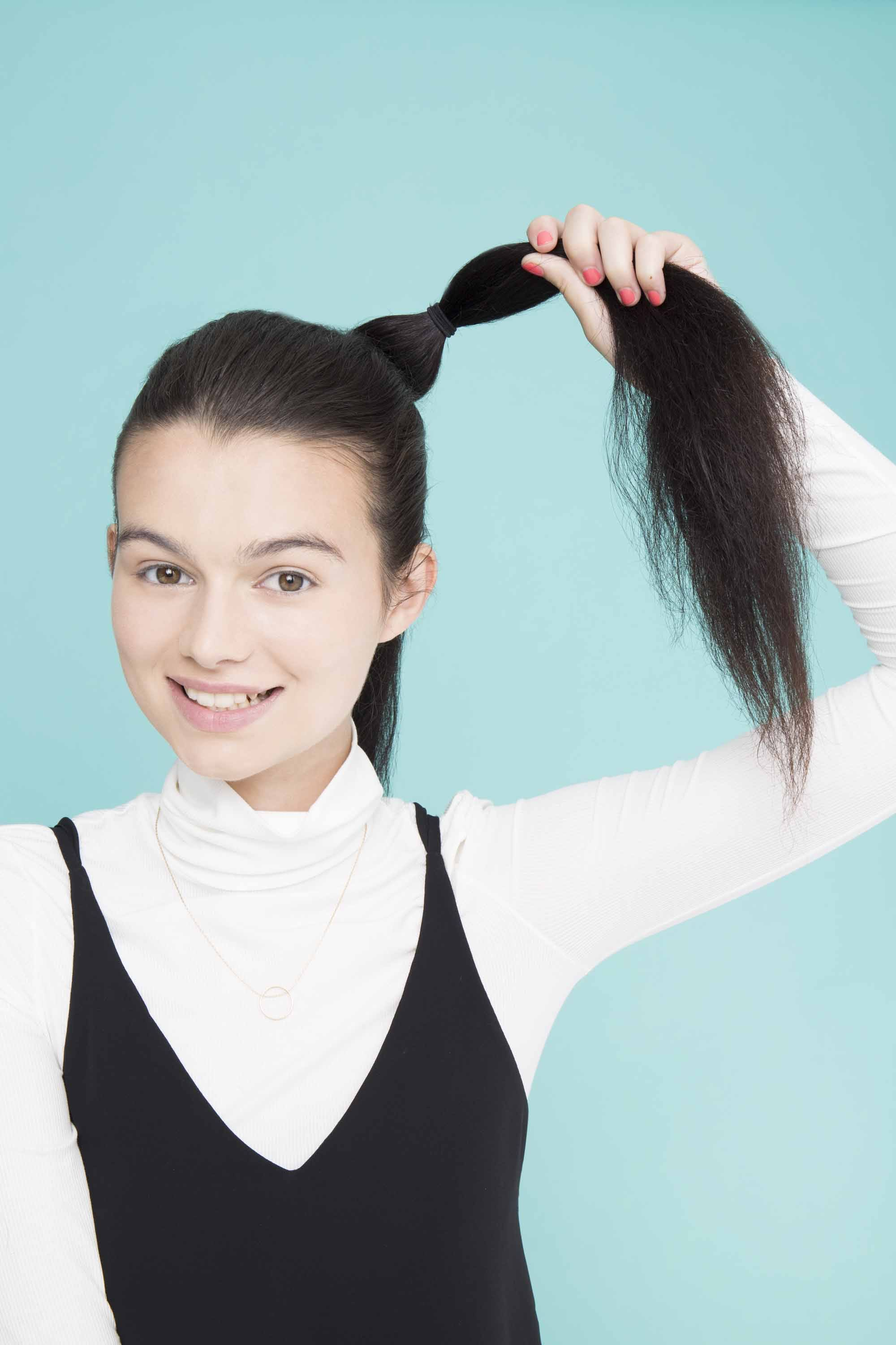 young lady with long black hair pull through braid ponytail tie bottom