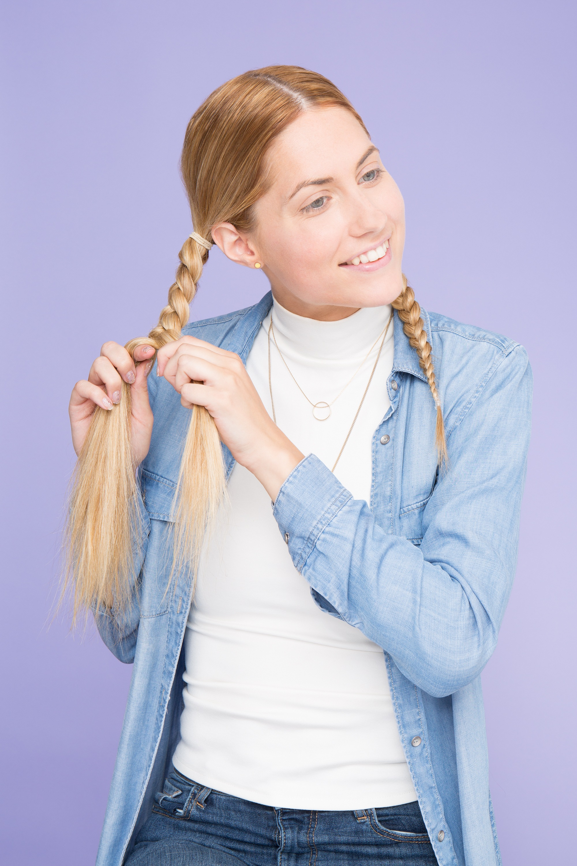 a blonde woman making braided pigtail of her hair smiling aside